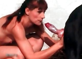 Slender redheaded slut gives a BJ to a doggo